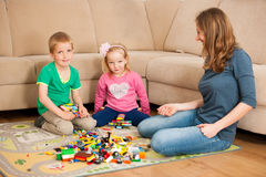 Children and their mother are playing with blocks on the ground Stock Photos