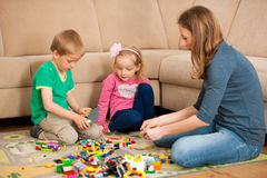 Children and their mother are playing with blocks on the ground Royalty Free Stock Photos
