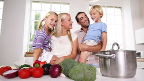 Children in their parents arms in the kitchen Royalty Free Stock Image