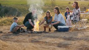Two family of six people at a picnic. Children with their parents around the campfire roasting sausages and bacon on skewers. Two family of six people at a stock video footage