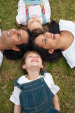 Children and their parents lying on the grass. Cute children and their parents lying on the grass in a park Stock Photography