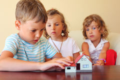 Children three together looking at model of house Royalty Free Stock Image