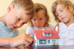 Children three together looking at model of house Stock Photography