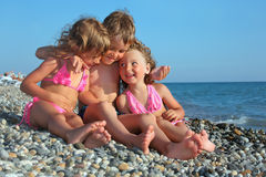 Children three together sitting on stony beach royalty free stock image