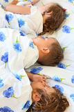 Children three together sleeping on bed. In cosy room Royalty Free Stock Image