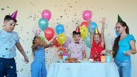 Children throw shiny confetti celebrating birthday at table