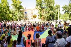 Children throw up ball together using multicolored linen in the sunny summer day. Komsomolsk-on-Amur, Russia - August 1, 2016. Public open Railroader`s day stock image