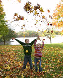 Children throwing leafs Royalty Free Stock Image