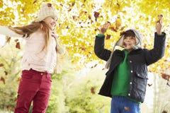 Children Throwing Leaves In Autumn Garden Stock Photo
