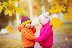 Children throwing leaves in beautiful autumnal day stock photos