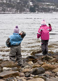 Children throwing rocks. Two children standing on a rocky beach, throwing stones into the sea Stock Image
