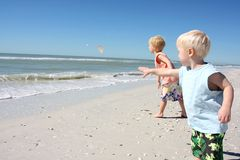 Children Throwing Seashells into the Ocean Royalty Free Stock Image
