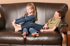 Children tickling feet. Cute little girl tickling brother's feet Stock Photography