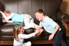 Children tickling feet. Cute kids tickling sister's feet Stock Photos