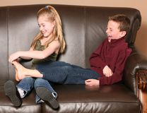 Children tickling feet. Cute little girl tickling brother's feet Royalty Free Stock Image
