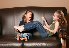 Children tickling feet. Cute little girl tickling sister's feet Stock Photography