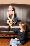 Children tickling feet with feather. Cute little girl tickling sister's feet with feathers Royalty Free Stock Photography