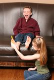Children tickling feet with feather. Cute little girl tickling boy's feet with feathers Stock Photo