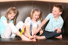 Children tickling feet with feather. Three cute kids tickling each other's feet with feathers Royalty Free Stock Images