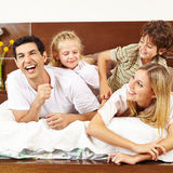 Children tickling parents in bed Stock Photography