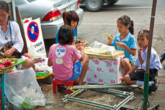 Children tie flowers at the flower market in Bangkok Stock Photo