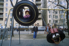 Children on tire swing in park Stock Photos