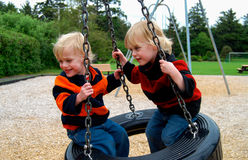 Children on Tire Swing. Twin boys play on tire swing at a neighborhood play ground Royalty Free Stock Image