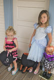 Children to Trick or Treat, Halloween. Two sisters,a toddler and her older sister, with brown hair and brown eyes and blond hair and blue eyes, stand at the door Stock Images
