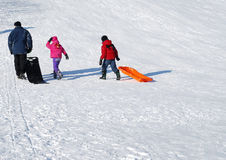 Children on a toboggan hill. Children climbing up on a toboggan hill stock images