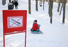 Children are tobogganing near prohibiting sign Royalty Free Stock Images