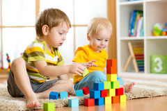 Children toddler and preschooler boys playing toy blocks at home or nursery Royalty Free Stock Image
