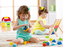 Children toddler and preschooler girls play logical toy learning shapes, arithmetic and colors at home or nursery Royalty Free Stock Photo