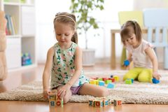 Children toddlers girls play toys at home, kindergarten or daycare centre. Children kid and toddler girls playing with toys at home, kindergarten or daycare stock photos