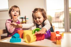 Children toddlers girls play toys at home. Kindergarten or nursery stock photo