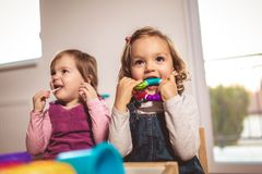 Children toddlers girls play toys at home. Kindergarten or nursery royalty free stock images