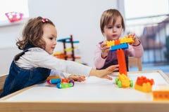 Children girls play toys at home, kindergarten or nursery. Children toddlers girls play toys at home, kindergarten or nursery stock photo