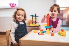 Children girls play toys at home, kindergarten or nursery. Children toddlers girls play toys at home, kindergarten or nursery stock image