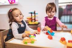 Children girls play toys at home, kindergarten or nursery. Children toddlers girls play toys at home, kindergarten or nursery stock photography