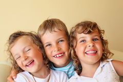 Children together in cosy, girl at left closed eye Royalty Free Stock Image
