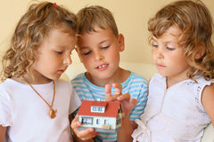 Children together keeping in hands model of house Stock Photo