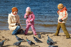 Children together with mum feed birds on autumn Royalty Free Stock Image