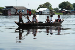Group of Children Traveling by Boat in Floating Village Stock Photos