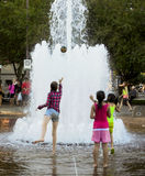 Children tossing ball into Fountain. One young teenage girl tosses a ball into a fountain. Two younger girls look on Stock Photos