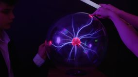 Children touches to plasma globe. Children are touching to the plasma globe in scientific museum. Tesla globe with electric impulses inside. The museum of stock video footage