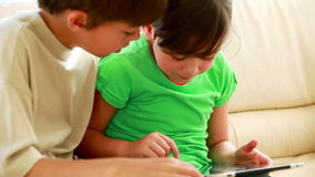 Children touching a tablet computer. In the living room stock footage