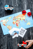 Children tourism outfit with map and pictures on dark background flat lay Stock Image
