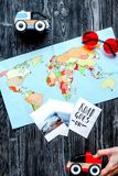 Children tourism outfit with map and pictures on dark background. Children tourism outfit with map and pictures on dark desk background flat lay Royalty Free Stock Photos
