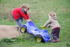 Children with toy car outdoors Stock Photos