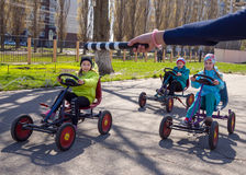 Children on toy cars execute commands of the regulator. Voronezh, Russia - April 26, 2017: Children on toy cars execute commands of the regulator Royalty Free Stock Images