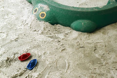 Children toy in a sandbox. A toy ship & turtle in a children playground sandbox stock image